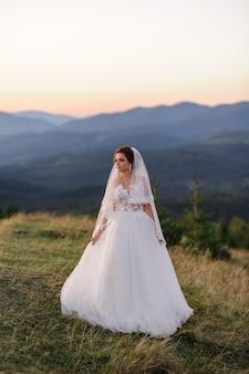 Одинокая невеста, покрытая вуалью, смотрит на закат в горном пейзаже.