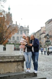 Семья с одной дочерью обнимаются и веселятся вместе.
