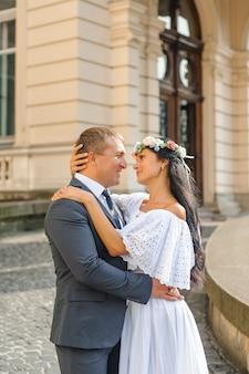 古い建物の背景での結婚式のフォトセッション。新郎新婦は優しく抱き合っています。