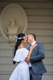 古い建物の背景での結婚式のフォトセッション。新郎新婦がキスします。キスの少し前に撮影しました。素朴または自由奔放に生きるスタイルの結婚式の写真