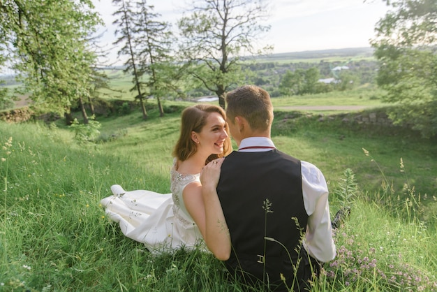 Жених и невеста сидят на зеленой траве.