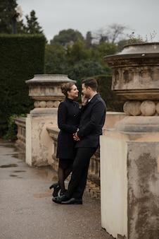 Молодая красивая испанская пара в любви обнимается в дождь перед национальным музеем искусств каталонии. застрелен на фоне площади испании в барселоне.