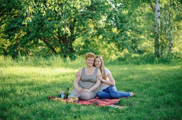 大人の娘が公園で屋外の年上の母親を抱擁します。