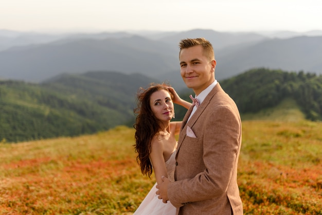 新郎新婦は優しく抱き合っています。日没。秋の山を背景に結婚式の写真。強い風が髪と服を膨らませます。閉じる。