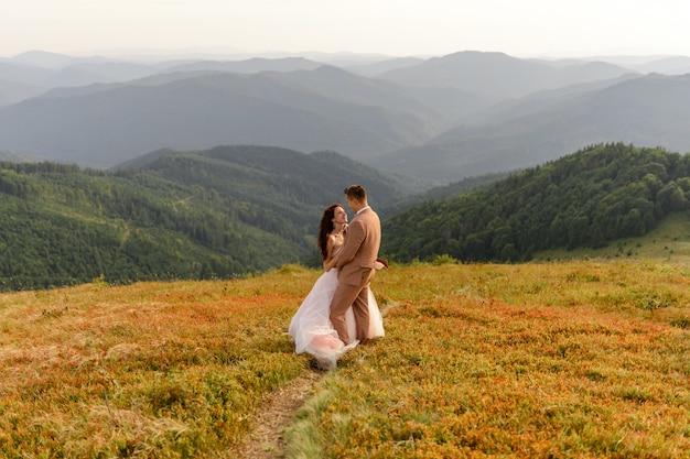 新郎新婦が抱いています。日没。秋の山を背景に結婚式の写真。強い風が髪と服を膨らませます。閉じる。
