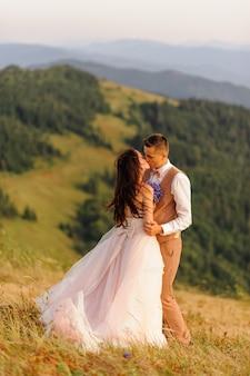 秋の山を背景に新郎新婦にキスします。日没。結婚式の写真。