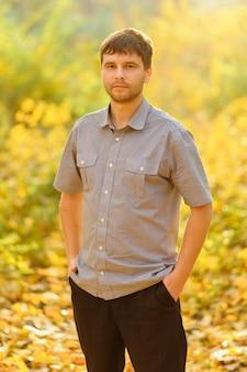 黄色の秋の背景に男の秋の肖像画。男性がカジュアルな服を着ています。
