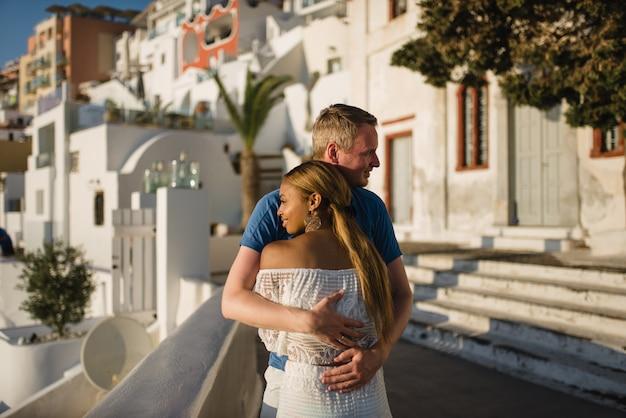 Влюбленная пара гуляет по улицам старого города на острове санторини.