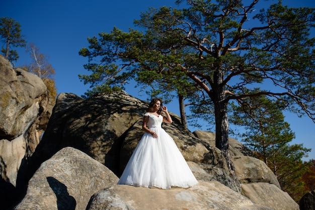 山の背景に日焼けした花嫁の肖像画。エンドウ豆で旅行中の結婚式後の写真撮影...