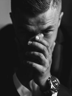 動揺の実業家のポートレート、クローズアップ。ビジネス危機の概念。男が頭の近くで手をつないでいます。手にセレクティブフォーカス。