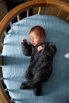 Маленький новорожденный мальчик спит в своей кроватке.