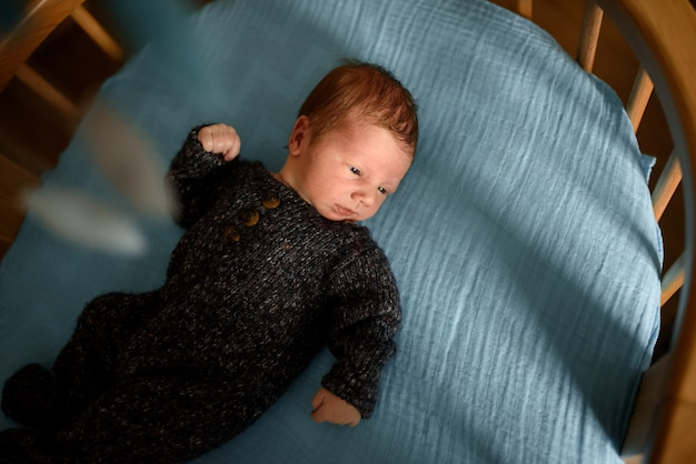 Маленький новорожденный мальчик смотрит в окно в своей кроватке.
