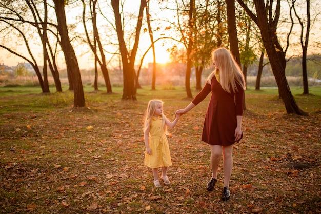 Мама и дочка в платьях гуляют за руку в осеннем парке.