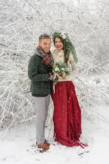 Молодожены обнимаются в зимнем лесу