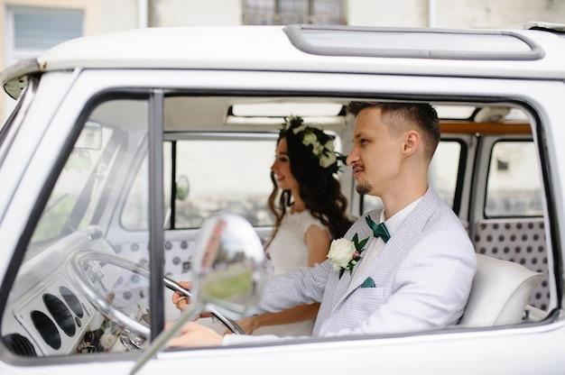 Жених и невеста сидят за рулем своего ретро-автобуса