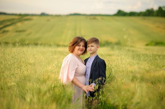 緑の麦畑の母と息子どちらも手を握る