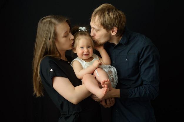 Отец и мать целуют свою маленькую годовалую дочь