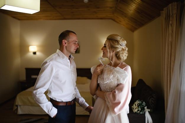 シルクのバスローブを着た花嫁がドレスを着ようとしています。彼女は婚約者に抱かれています。新郎新婦が一緒に結婚式の準備をしています