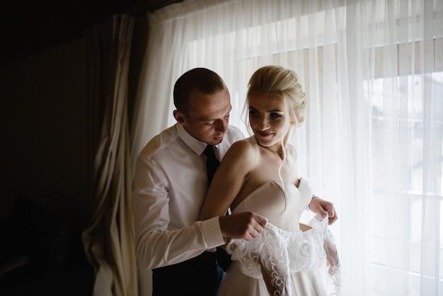 結婚式の準備をしている白い豪華なドレスを着た豪華な金髪の花嫁