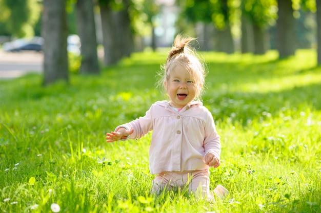 緑の芝生に膝の上に座っているカジュアルな服装でかわいい女の子