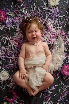 花の花輪と甘い小さな女の赤ちゃんの肖像画