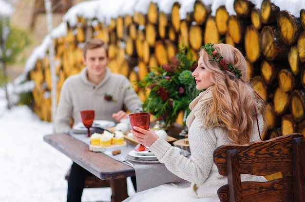 新郎は寺院で彼の花嫁にキスします。木製の背景に雪の上に花束と新婚夫婦が座っています。冬の結婚式