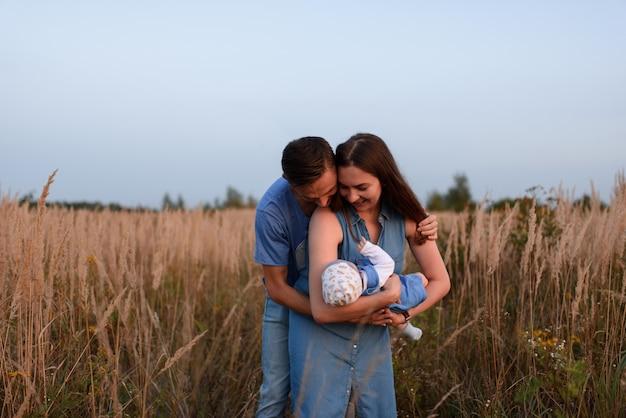 Молодые родители гуляют с маленьким сыном в поле