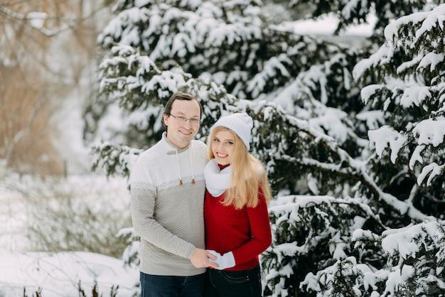 Счастливая пара взрослых весело в зимнем лесу и улыбаясь, копией пространства