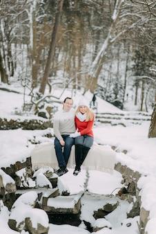 Молодая влюбленная пара в зимних куртках и шарфах сидит в снежном парке