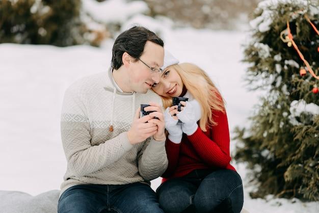 お茶を飲むとそりの上に座って冬の幸せなカップル