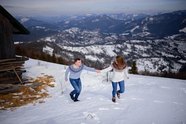 男と女が雪に覆われた山で遊ぶニット服を着ています。