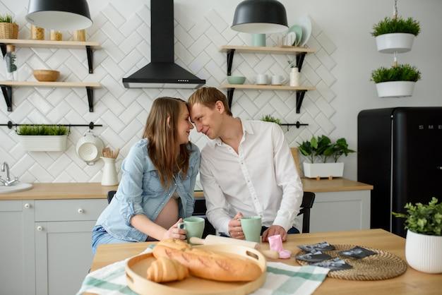 Беременная пара в любви сидит на кухне