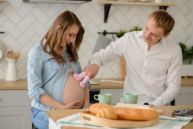 Будущий отец со своей беременной женой, держащей маленькие детские носки рядом с