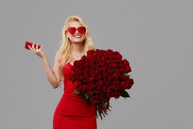赤いバラと携帯電話の大きな花束を保持しているハート形のメガネで幸せな若いブロンドの女性