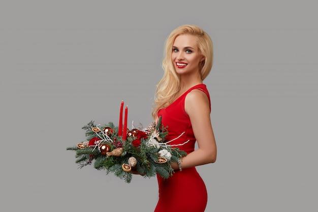 赤いドレスを着た若いブロンドの女性は彼女の手でクリスマスリースを保持しています。中立的な灰色の背景に花とクリスマスツリーの枝のお祝い花束