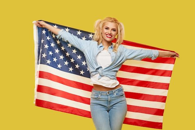 黄色の背景に分離された米国旗を保持しているデニムの服で幸せな若い女