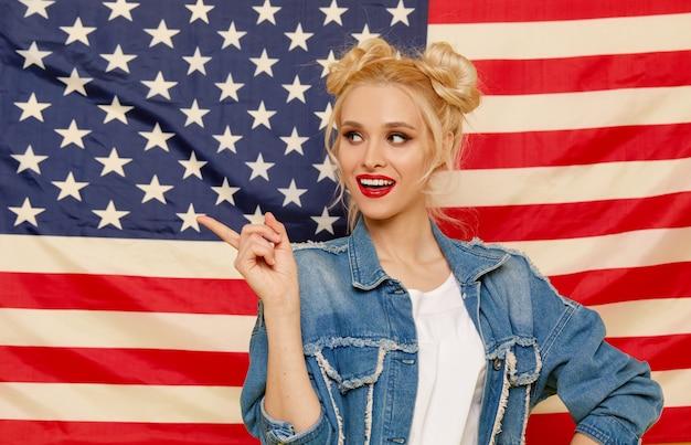 Американская девушка. портрет счастливой молодой удивленной женщины на предпосылке флага сша.