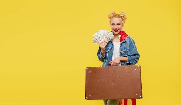 Молодая женщина с американским флагом держит в руках дорожный чемодан и денежные купюры. удивленное веселое лицо.