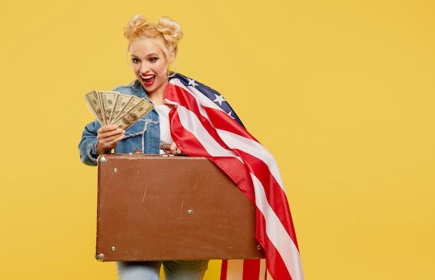 Молодая девушка с американским флагом держит в руках дорожный чемодан и денежные купюры. удивленное веселое лицо.