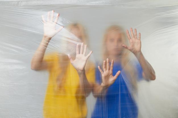 Молодые женщины-добровольцы в желтых и синих футболках проводят кампанию против использования полиэтилена и пластика. концепция утилизации отходов