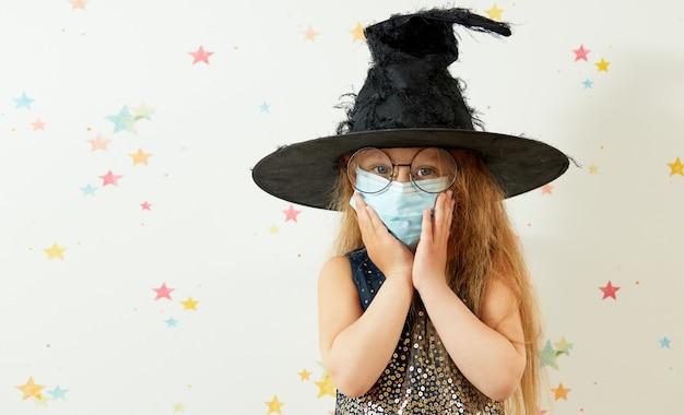 Счастливого хэллоуина . маленькая девочка ребенок в ведьма карнавальный костюм и маска для защиты лица.