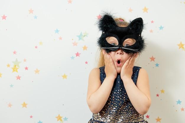 Счастливого хэллоуина . маленькая девочка ребенок в маске черного кота, карнавальный костюм. смешное лицо