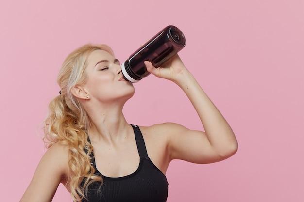 広告パーソナルトレーニング。若いスポーティな女性が室内でトレーニングした後、シェーカーからプロテインシェークを飲みます。ピンクの壁