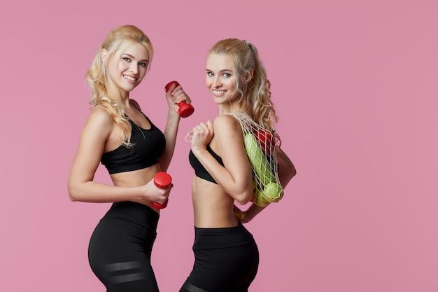 Спортсменка молодых женщин с гантелями и свежими овощами в сумке строки. концепция здорового питания и диеты.