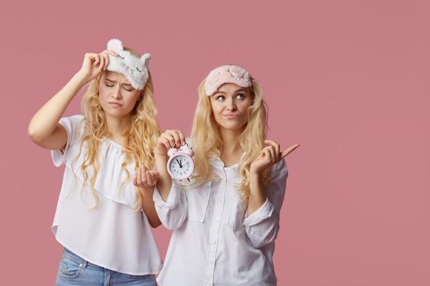 Две односпальные бессонные молодые женщины в пижамах и снах на розовой стене. будильник разбудил женщину