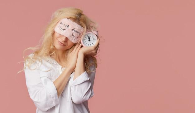 ピンクの壁にパジャマと睡眠マスクでリラックスした若い女性。目覚まし時計が少女を起こした