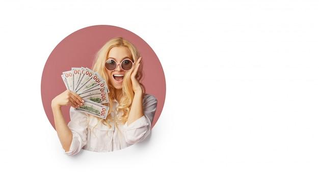 Портрет молодой женщины в шоке с пачкой банкнот и текст продажа. подглядывание в белую дыру забавное лицо с открытым ртом. вау концепция