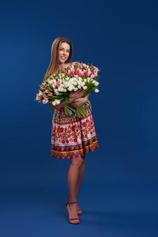 贈り物に最適です。女性の日の素晴らしい花。大きな花束の色とりどりのチューリップで優しい笑顔の黒髪の女性のポーズは、幸せそうに見えます。テキストのためのスペース