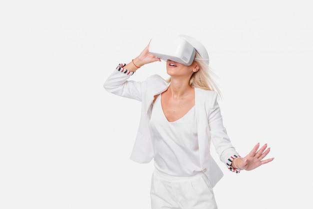 Белокурая женщина в белом номере с очки виртуальной реальности. студия выстрелил на пустое пространство