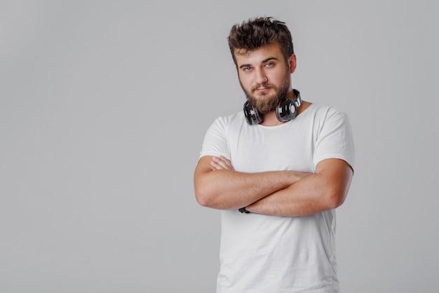Молодой человек с бородой с беспроводными наушниками на шее